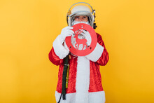 Santa Claus In Astronaut Helmet With A Reindeer Traffic Sign On Yellow Background. Christmas Concept