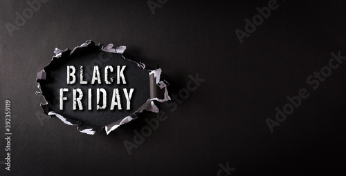 Top view of black torn paper and the text Black Friday on backboard background. Black Friday composition.