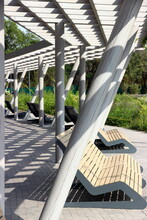 Design Benches In A Park With A Canopy Of Sun With Shadows On The Pavement
