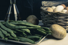 View Of Green Beans, Potatoes, A Bottle Of Olive Oil, And Eggs In A Basket On A Table