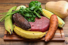 Closeup Of Fresh Meat, And Various Vegetables On A Wooden Cutting Board