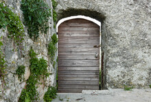Old Wooden Door In A Stone Arch