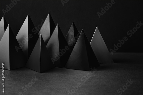 Fototapeta Prism pyramid objects on black gray background. Abstract geometrical figures still life composition. obraz