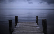 Cloudy Landscape, On The Horizon Of The Sea And Sky An Old Wooden Bridge For Fishermen And Small Boats. Melancholic Mood And Calmness. Minimalism In Nature. Calm Water And Sky