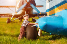 A Small Child Stands Near An Old Sightseeing Plane And Waits For His Father A Mechanic