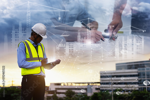 Obraz Engineering Consulting People on construction site holding tablet in his hand. Management in business workflow and Building inspector with BIM technology in Construction Project. - fototapety do salonu
