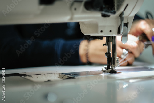 Fototapeta Closeup of female hands sewing gray leather on a machine
