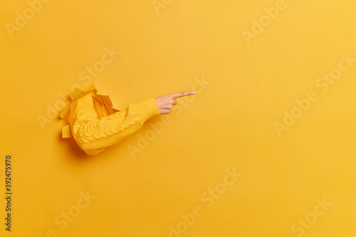 Obraz Faceless woman breaks arm through paper yellow wall indicates on right at blank space gives advice to buy subscription suggests to click on link shows direction. Place for your advertisement - fototapety do salonu