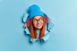 Leinwandbild Motiv Positive redhead young woman looks away with pleasant smile has curious expression wears hat and optical glasses breaks through blue paper background. Millennial girl has foxy hair happy smile