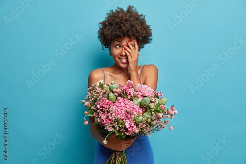 Tela Photo of cheerful shy African American woman hides face with palm smiles happily wears dress holds big bouquet of flowers isolated over blue background