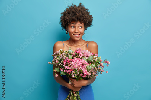 Tablou Canvas Pretty satisfied dark skinned young woman has Afro hair holds bunch of flowers bites lips and looks away receives bouquet on festive event poses against blue background
