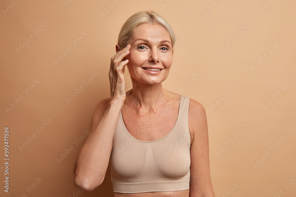 Fototapeta Portrait of charming forty years old blonde woman takes care of complexion enjoys softness of skin touches face gently wears cropped top poses against beige studio wall. Beauty and aging concept