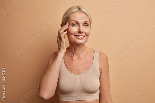 Portrait of charming forty years old blonde woman takes care of complexion enjoys softness of skin touches face gently wears cropped top poses against beige studio wall. Beauty and aging concept