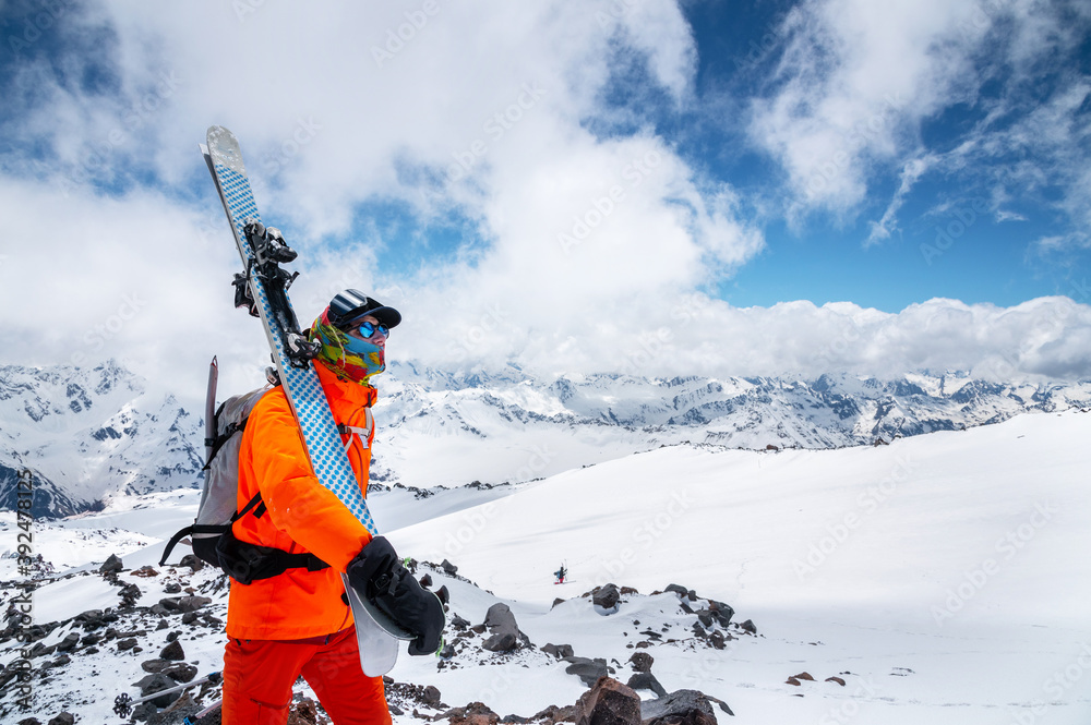 Leinwandbild Motiv - yanik88 : Portrait of a stern climber skier in sunglasses and a cap with a ski mask on his face. holds his skis on his shoulder and looks away against of Mount Elbrus
