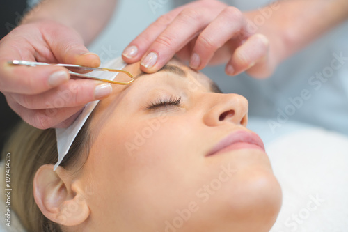 beautician doing eyebrows of a woman in cosmetic studio Fototapet
