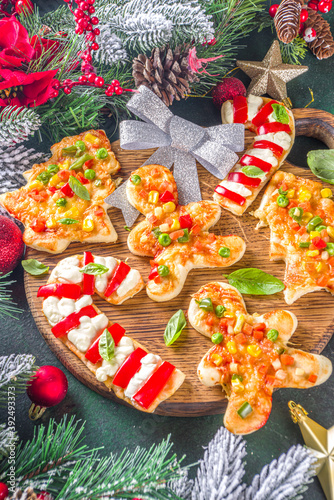 Christmas Pizza for child dinner, made with cookie cutters, in form of Christmas Traditional Symbols - Candy Cane, Gingerbread man, Xmas tree, funny food for New Year party