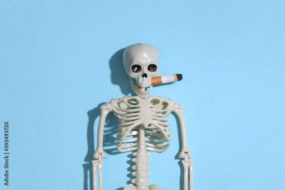 Fototapeta Smoking skeleton with a cigarette in the mouth against a bright blue background. Smoking kills
