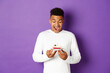 Leinwandbild Motiv Portrait of happy young african-american man celebrating his birthday, looking at b-day cake and smiling, making wish, standing over purple background