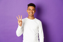 Image Of Cheerful African-american Guy In White Sweatshirt, Showing Three Fingers And Smiling, Standing Over Purple Background