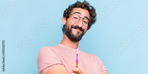young bearded man looking like a happy, proud and satisfied achiever smiling wit Wallpaper Mural