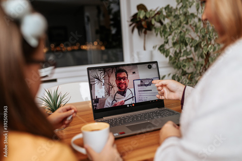 Fototapeta Middle age doctor talking and examining little girl using laptop computer and internet connection. They are chatting while doctor gives health advices. Telehealth concept. obraz
