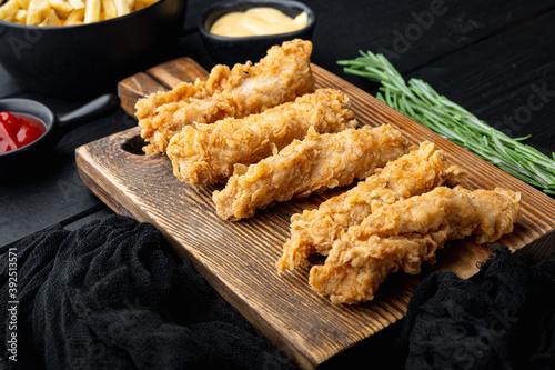 Fototapeta Crispy chicken tenders on black wooden background obraz
