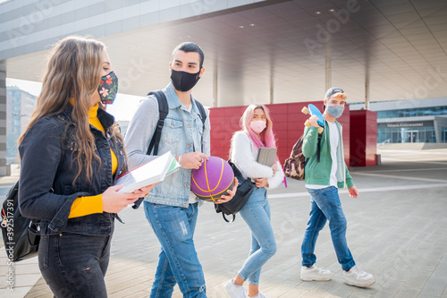 Foto Multiracial students with face mask walking speaking wearing protective mask dur