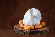 Fall Harvest, White Ceramic Turkey Surrounded By Chocolate Shaped As Pumpkins, Corn, And Pinecones, On A Wooden Cake Stand, Against A Brown Background