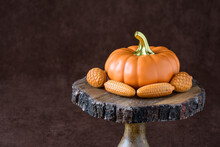 Fall Harvest, Orange Ceramic Pumpkin Surrounded By Chocolate Shaped As Walnuts And Corn, On A Wooden Cake Stand, Against A Brown Background