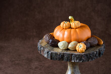 Fall Harvest, Orange Ceramic Pumpkin Surrounded By Chocolate Shaped As Walnuts, Pinecones, Corn, And A Pumpkin, On A Wooden Cake Stand, Against A Brown Background