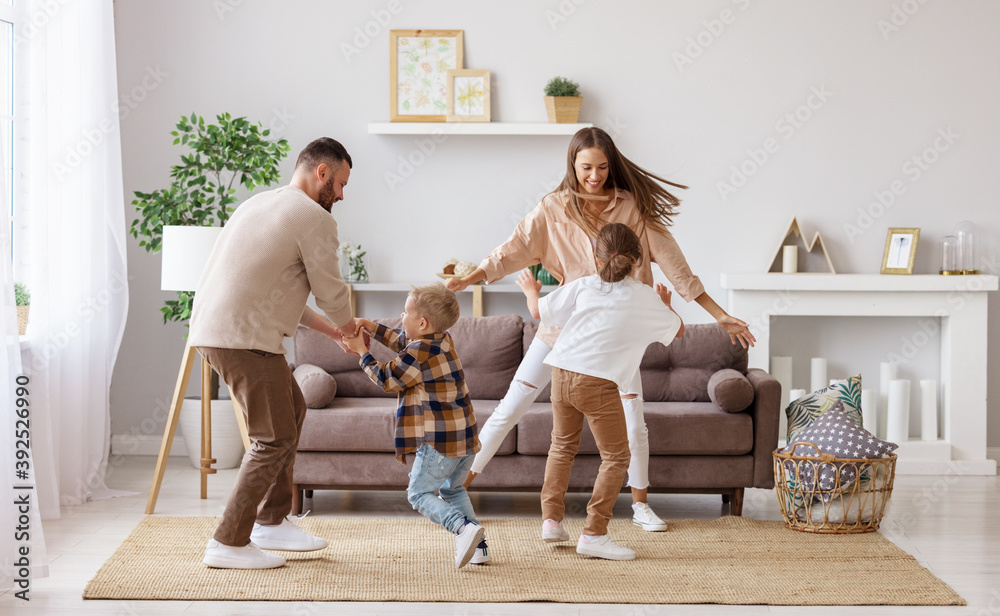 Fototapeta happy family mother father and children dancing at home  .