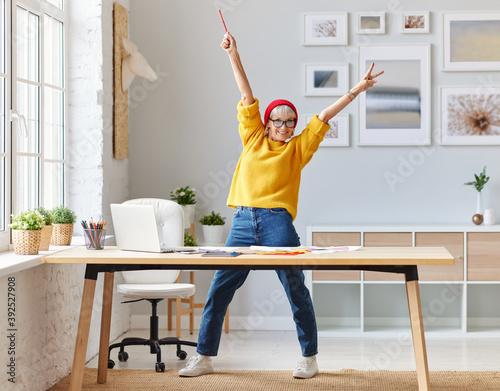 Obraz cheerful elderly woman freelancer creative designer in a red hat having fun and dancing in workplace. - fototapety do salonu
