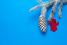 Spruce Branch With A Cone In The Snow And Decoration In The Form Of An Angel On A Blue Background.