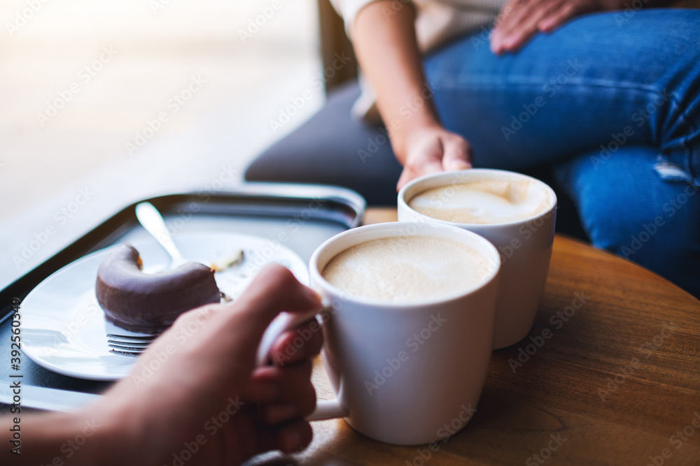Fototapeta Closeup image of two people clink white coffee mugs on wooden table in cafe