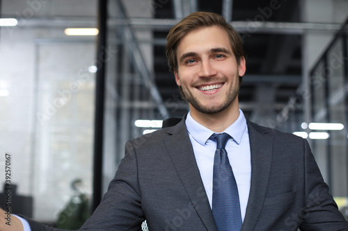 Young handsome businessman smiling in an office environment