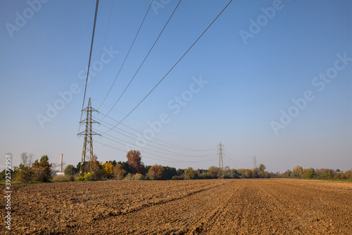 Fotografia Ploughed field in autumn with an electricity pylon in the middle of it
