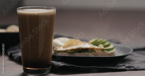Slow motion stout beer in pint glass with food on background Fotobehang