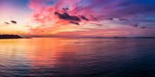 A Beautiful Sunset Over The Calm Sea With Red, Orange And Pink Clouds Reflecting In The Water