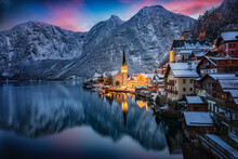 The Little Village Of Hallstatt, Austria, During Winter Dusk Time With Snow, Glowing Sky In The Mountains And Warm Lights From The Houses