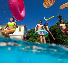 Split Underwater Photo Of Many Kids Have Fun In The Swimming Pool Diving With Inflatable Toys Doughnuts Jump And Splash In The Water