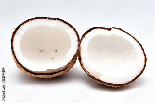 Vászonkép Healthy food - Halved coconut isolated on white background.
