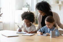 Smiling African American Woman, Caring Mother Helping Two Little Daughters With Homework, Multiracial Pretty Girls Sisters Sitting At Table In Kitchen, Studying, Writing Or Drawing, Homeschooling