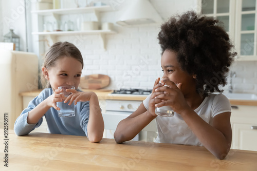 Fototapeta African American and Caucasian cute little girls drinking pure water together, sitting at wooden table in kitchen, pretty kids holding glasses of fresh aqua, refreshment and hydration concept obraz na płótnie