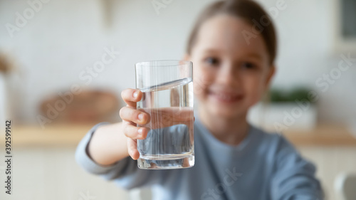Obraz na plátne Close up smiling little girl holding glass of pure mineral water, offering to ca