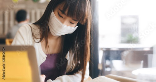 Photo Young adult asian student female with face mask for virus corona or covid 19 study at cafe
