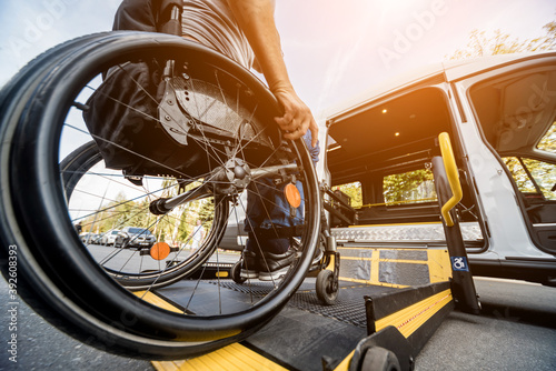 A man in a wheelchair moves to the lift of a specialized vehicle Billede på lærred