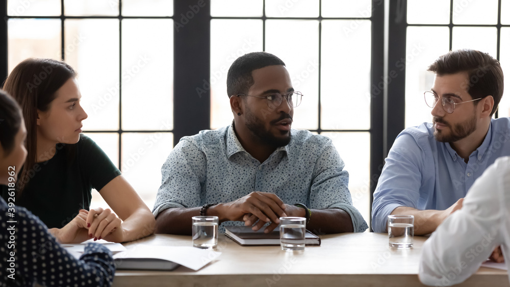 Fototapeta Starting workday from briefing. Confident serious african american ceo leader chief speaking to diverse staff group on formal meeting in office, black millennial employee proposing idea to colleagues