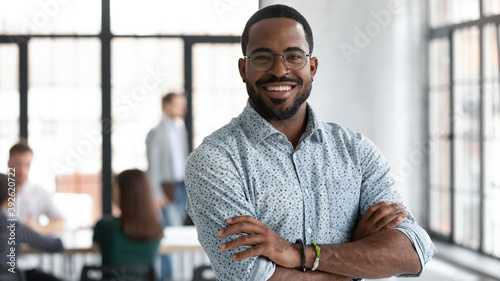 I made this. Portrait of ambitious confident black leader ceo standing with arms crossed on chest at office of successful profitable company looking at camera proud of his achievement career wellbeing