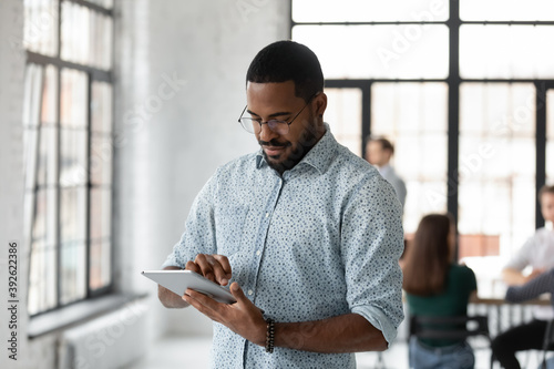 Obraz Easy communication. Busy concentrated young black male employee manager corporate worker standing at office open space focused on tablet pc screen accepting urgent order reading email texting answer - fototapety do salonu