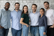 When Colleagues Are Friends. Group Portrait Of Happy Positive Diverse Young People Of Different Gender And Race Coworkers Teammates Standing By Brick Wall Close Together Hugging And Looking At Camera